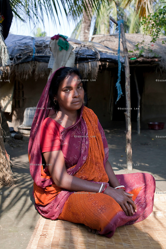 Tiger attack survivor Tarubala Mandol, 30, speaks of the attack as she sits in front of her home on Gosaba island, Sundarban, West Bengal, India, on 18th January, 2012. 1.5 years ago, she was pounced on by a waiting tiger outside her home. She survived as the tiger was chased away and tranquilized when it hid in the forest goddess Bono Debi/Bono Bibi temple nearby. Tigers have been known to swim, sometimes underwater, to the village to hunt humans. A successful Royal Bengal tiger breeding program has increased their numbers but decreased the number of husbands. There are now an estimated 3,000 widows in the villages where their husbands, have been killed by tigers. Photo by Suzanne Lee for The National (online byline: Photo by Szu for The National)