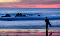 The sun sets on Pfiffer Beach in Big Sur California.  A surfer appears not yet ready to call it a day as he looks out at the colorful sunset.