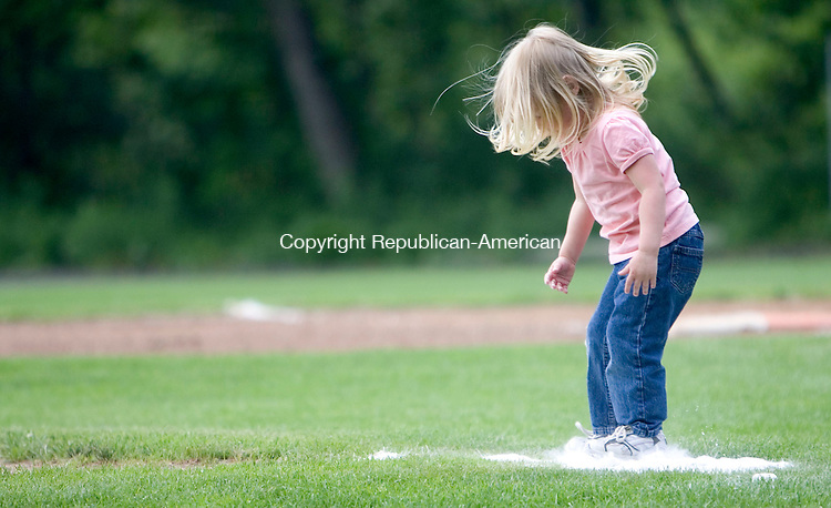 TORRINGTON, CT- 25 JUNE 2008- 062508JT02-<br /> Eliana Knapp, of Torrington, who just turned three on Tuesday, jumps on a pile of chalk on the softball field in Joe Ruwet Park on Wednesday afternoon in Torrington.<br /> Josalee Thrift / Republican-American