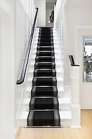 Steel stair rods hold a black and grey stair runner in place on staircase