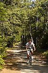 Pebble Beach on Moosehead Lake, ME with teenager riding mountain bike on penisula path.
