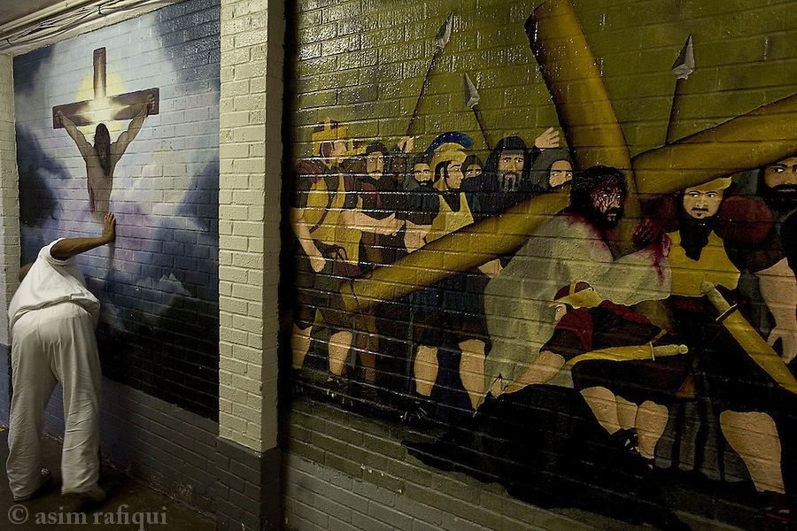 An inmate on cleaning duty with christian religious murals decorating the walls of the prison<br />
