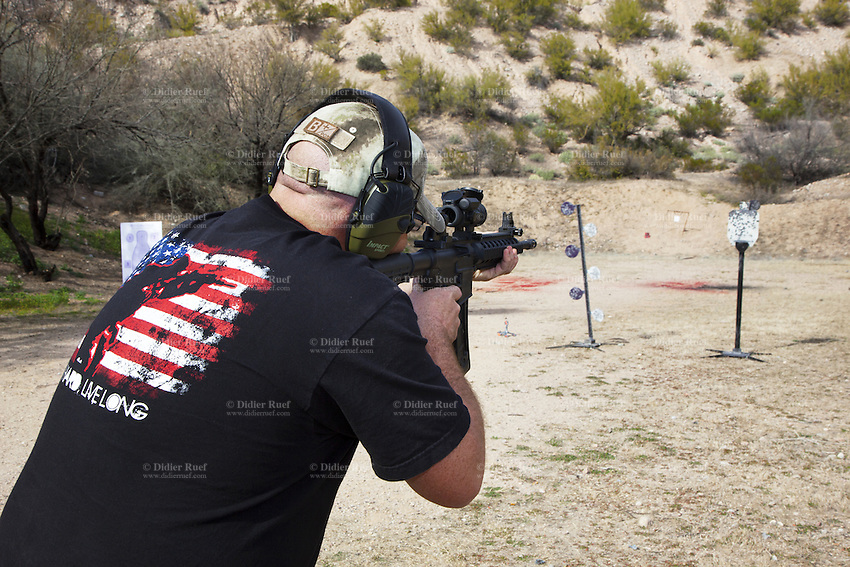 """USA. Arizona state. Kearny town. Copper Basin Sportsmen's Club. Chance  Drew Stonecipher is training his shooting skills on a target with a Smith & Wesson M&P15-22 which is a semi-automantic rifle. He is wearing a  cap with his B+ blood type and a black t-shirt with a U.S. soldier and an american flag. The flag of the United States of America, often referred to as the American flag, is the national flag of the United States. It consists of thirteen equal horizontal stripes of red (top and bottom) alternating with white, with a blue rectangle in the canton (referred to specifically as the """"union"""") bearing fifty small, white, five-pointed stars arranged in nine offset horizontal rows of six stars (top and bottom) alternating with rows of five stars. Copper Basin Sportsmen's Club is a membership Range complex which purpose is to promote the sport of shooting and providing a safe, fun, family oriented environment. A firearm is a portable gun, being a barreled weapon that launches one or more projectiles often driven by the action of an explosive force. Most modern firearms have rifled barrels to impart spin to the projectile for improved flight stability. The word firearms usually is used in a sense restricted to small arms (weapons that can be carried by a single person). The right to keep and bear arms is a fundamental right protected in the United States by the Second Amendment of the Bill of Rights in the Constitution of the United States of America and in the state constitutions of Arizona and 43 other states. 29.01.16 © 2016 Didier Ruef"""