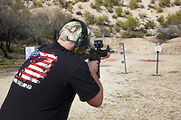 "USA. Arizona state. Kearny town. Copper Basin Sportsmen's Club. Chance  Drew Stonecipher is training his shooting skills on a target with a Smith & Wesson M&P15-22 which is a semi-automantic rifle. He is wearing a  cap with his B+ blood type and a black t-shirt with a U.S. soldier and an american flag. The flag of the United States of America, often referred to as the American flag, is the national flag of the United States. It consists of thirteen equal horizontal stripes of red (top and bottom) alternating with white, with a blue rectangle in the canton (referred to specifically as the ""union"") bearing fifty small, white, five-pointed stars arranged in nine offset horizontal rows of six stars (top and bottom) alternating with rows of five stars. Copper Basin Sportsmen's Club is a membership Range complex which purpose is to promote the sport of shooting and providing a safe, fun, family oriented environment. A firearm is a portable gun, being a barreled weapon that launches one or more projectiles often driven by the action of an explosive force. Most modern firearms have rifled barrels to impart spin to the projectile for improved flight stability. The word firearms usually is used in a sense restricted to small arms (weapons that can be carried by a single person). The right to keep and bear arms is a fundamental right protected in the United States by the Second Amendment of the Bill of Rights in the Constitution of the United States of America and in the state constitutions of Arizona and 43 other states. 29.01.16 © 2016 Didier Ruef"