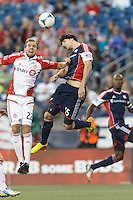 Toronto FC forward Jeremy Brockie (22) and New England Revolution defender Stephen McCarthy (15) battle for head ball. In a Major League Soccer (MLS) match, Toronto FC (white/red) defeated the New England Revolution (blue), 1-0, at Gillette Stadium on August 4, 2013.
