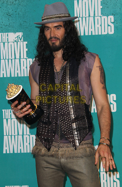 Russell Brand.2012 MTV Movie Awards held at the Gibson Amphitheatre, Universal City, California, USA..3rd June 2012.half length grey gray hat beard facial hair purple sleeveless top armpit sweat patch waistcoat tattoo award trophy winner  .CAP/ADM/SLP/LS.©Lee Sherman/Starlitepics/AdMedia/CapitalPictures.