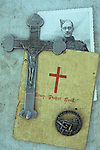 Vintage photo of man in World War 2 army uniform lying with grey metal crucifix Army prayer book and Maginot Line badge