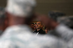 Sgt. 1st Class Jeremiah Mock is framed by a saluting soldier during a memorial service for three Nevada National Guard members killed earlier this week by a gunman in an IHOP restaurant. Mock was one of seven people also injured in the attack and honored during the private memorial in Carson City, Nev., Sunday afternoon, Sept. 11, 2011. (AP Photo/Cathleen Allison)