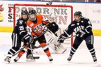 Yale's Kate Martini (25), Jaimie Leonoff (32), Tara Tomimoto (4), and RIT's Morgan Scoyne (3) await for the puck in the third period. RIT defeated Yale 3-0 at Blue Cross Arena in Rochester, New York on October 19, 2012