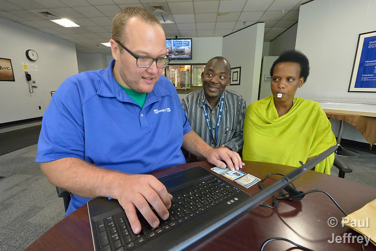 Tom Melissen (left), a senior account manager with Staff Management/SMX, completes an online employment application for Felecite Mukagatana in the Mars factory in Elizabethtown, Pennsylvania, as Joseph Shilalo, an employment specialist for Church World Service, looks on. Mukagatana, who has an oral swab for drugs in her mouth, is a refugee from the Democratic Republic of the Congo, and was applying for a job in the factory. She was helped by Church World Service, an agency that resettles refugees in Pennsylvania and other locations in the United States. She passed the drug test and was offered employment.<br /> <br /> Photo by Paul Jeffrey for Church World Service.