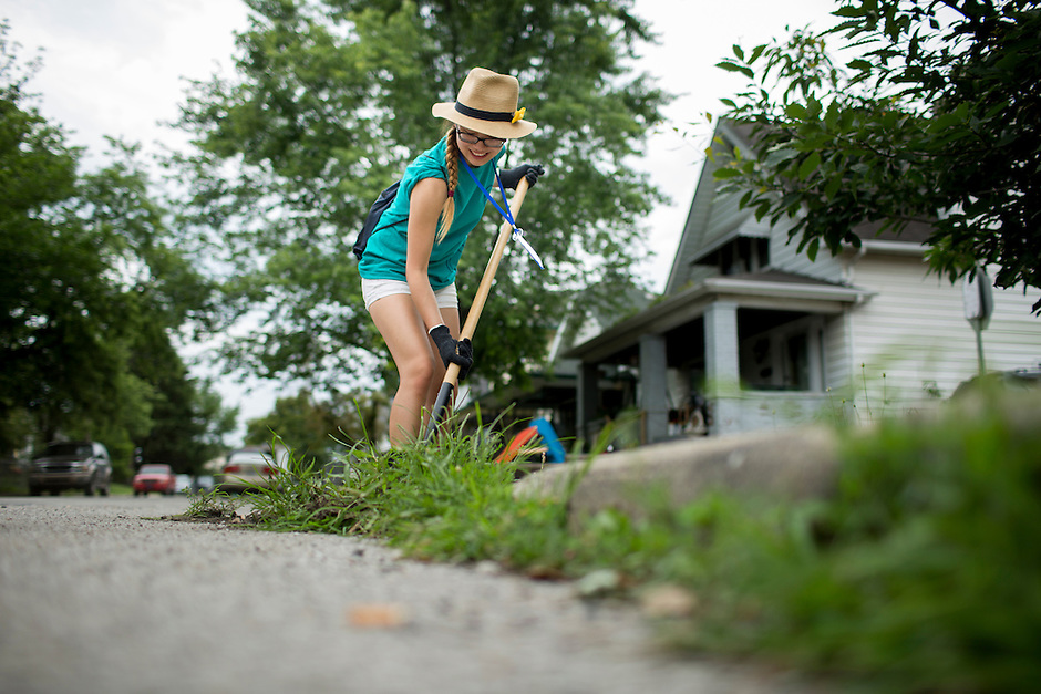 """Amber Huang digs up weeds along a curb in the Hawthorne neighborhood during """"Circle the City with Service,"""" the Kiwanis Circle K International's 2015 Large Scale Service Project, on Wednesday, June 24, 2015, in Indianapolis. (Photo by James Brosher)"""