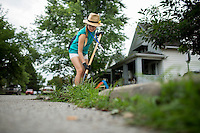 "Amber Huang digs up weeds along a curb in the Hawthorne neighborhood during ""Circle the City with Service,"" the Kiwanis Circle K International's 2015 Large Scale Service Project, on Wednesday, June 24, 2015, in Indianapolis. (Photo by James Brosher)"