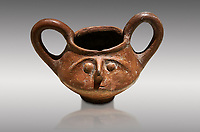 Hittite terra cotta double handled jug with a relief human face- 17th - 16th century BC - Hattusa ( Bogazkoy ) - Museum of Anatolian Civilisations, Ankara, Turkey. Against gray background