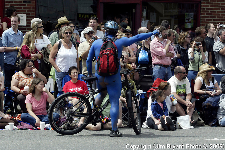 Painted in blue, a biker talks to parade watchers during the 21st annual Summer Solstice Parade Saturday, June 20, 2009 in Seattle.  The parade was held Saturday, bringing out painted and naked bicyclists, bands, belly dancers and floats. (Jim Bryant Photo © 2009) .