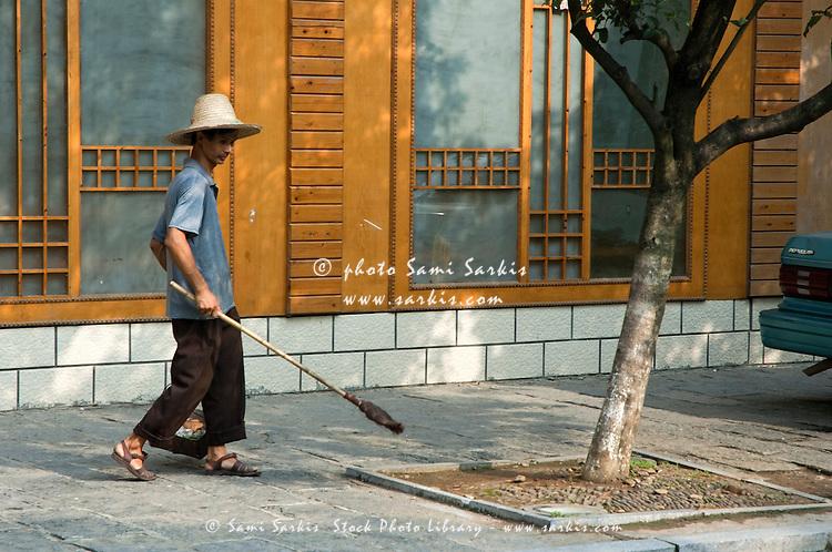Street sweeper at work in Yangshuo, Guangxi, China.