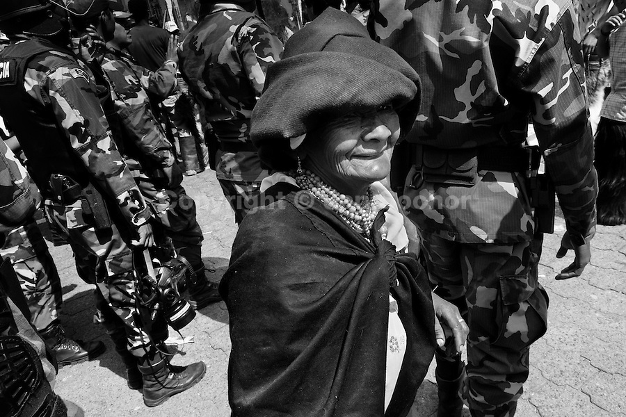 An old Indian woman walks in front the riot policemen during the Inti Raymi (San Juan) festivities in Cotacachi, Ecuador, 24 June 2010. 'La toma de la Plaza' (Taking of the square) is an ancient ritual kept by Andean indigenous communities. From the early morning of the feast day, various groups of San Juan dancers from remote mountain villages dance in a slow trot towards the main square of Cotacachi. Reaching the plaza, Indians start to dance around. They pound in synchronized dance rhythm, shout loudly, whistle and wave whips, showing the strength and aggression. Dancers from either the upper communities (El Topo) or the lower communities (La Calera), joined in respective coalitions, seek to conquer and dominate the square and do not let their rivals enter. If not moderated by the police in time, the high tension between groups always ends up in violent clashes.
