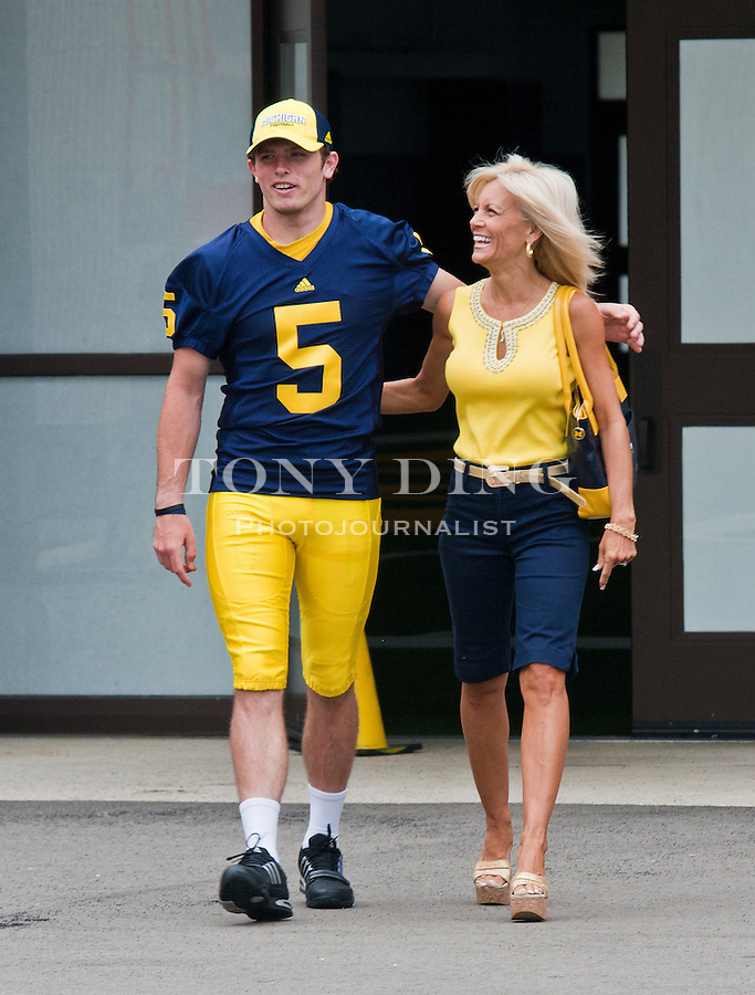 Michigan quarterback Tate Forcier (5) walks with head coach Rich Rodriguez's wife Rita at the annual NCAA college football media day, Sunday, Aug. 22, 2010, in Ann Arbor, Mich. (AP Photo/Tony Ding)