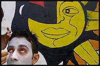 "An unidentified woman puts make up on Martin Beracochea, known as ""Farol"" as he gets ready for the inaugural parade of the Uruguayan Carnival, January 30, 2004. In an abandoned bar in the middle class neighbourhood of Sayago Murga Contrafarsa's members make their last preparations for the opening parade in !8 de Julio Av. in Montevideo Uruguay."