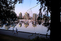 Apartment, office block reflections and joggers, English bay,Vancouver, Canada