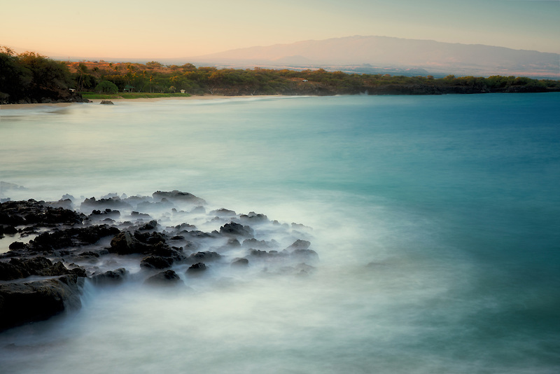 Beach and waves with Hualalai volcano in background. Hawaii Island