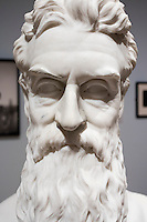"""A marble bust of abolitionist John Brown stands on a work table while conservators work on a replacement nose and eyebrow (left) in the Tisch Family Gallery at the Tufts University Art Gallery at Tufts University in Medford, Massachusetts, on Thurs., Oct. 6, 2016. The bust was sculpted by Edward Augustus Brackett and had been improperly stored for decades with a broken nose and eyebrow. The conservators, from Rika Smith McNally and Associates, found a plaster cast made from the original at the Boston Athenæum and had a 3D modeler image the broken section of the original and the cast. They then used 3D printing technology to use to create a plaster nose replacement that would fit perfectly on the broken marble bust. They then used gouache paint to match the replacement pieces to the original marble.  The bust is part of an exhibition at the gallery entitled """"Mortal Things: Portraits Look Back and Forth."""""""