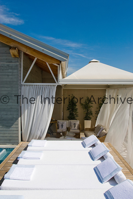 A view into the covered patio area is punctuated by the row of floor level sun loungers on the deck