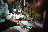 People of Burma believe in secrecy of moment of death. And the way person is sent in last way is very important.<br /> Proper funeral expenses in big city like Yangon can cost minimum 1000US dollars - amount impossible for poor families.<br /> On the photo: member of charity organization of free funeral services helps family of passed away person to fill all necessary papers before start transportation of the body. Reason of death:  cirrhosis of liver - one of the most frequent deceases in Burma because of cheap alcohol.