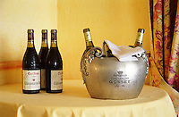 Three bottles of red Chateauneuf du Pape Excellence Cuvee Consuls 1998, three bottles of white Chateauneuf in an ice bucket engraved with champagne Gosset on a table in the restaurant La Mere Germaine in Chateauneuf  Chateauneuf-du-Pape Châteauneuf, Vaucluse, Provence, France, Europe  Chateauneuf-du-Pape Châteauneuf, Vaucluse, Provence, France, Europe