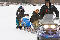 Nikolai volunteers deliver straw and dog food to a musher at the Nikolai checkpoint on Tuesday during Iditarod 2008