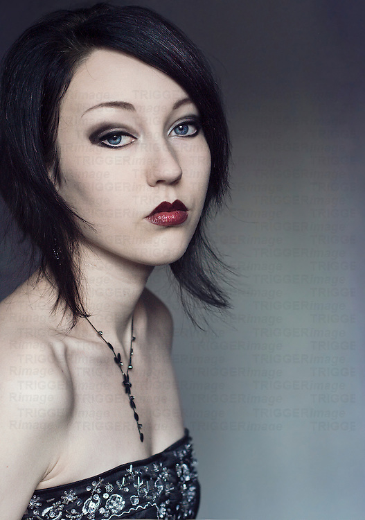 Young woman with black hair and blue eyes and pale skin, wearing a black embelished corset, looking into the camera with simple background.