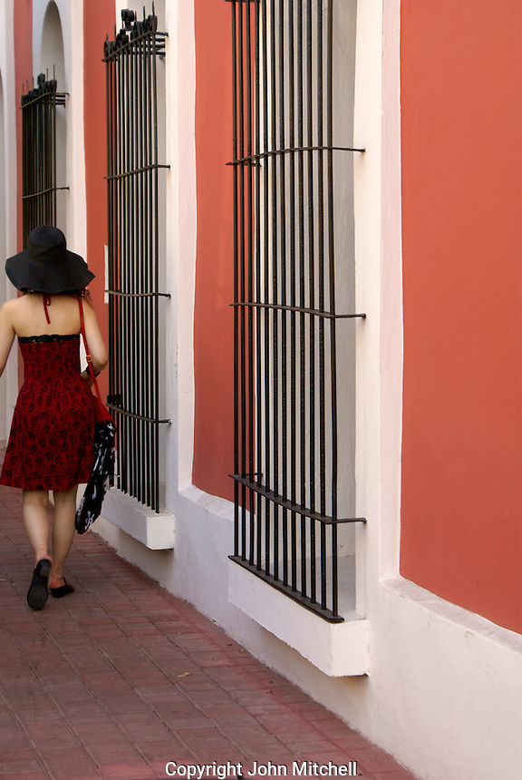 Stylishly dressed young woman walking down a street in Old Mazatlan, Sinaloa, Mexico