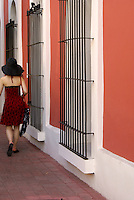 Stylishly dressed young woman walking down a street in Old Mazatlan, Sinaloa, Mexico
