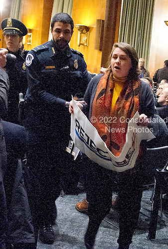 A protestor is led out of the United States Senate Committee on Foreign Relations hearing considering the nomination of Rex Wayne Tillerson, former chairman and chief executive officer of ExxonMobil to be Secretary of State of the US on Capitol Hill in Washington, DC on Wednesday, January 11, 2017.<br /> Credit: Ron Sachs / CNP