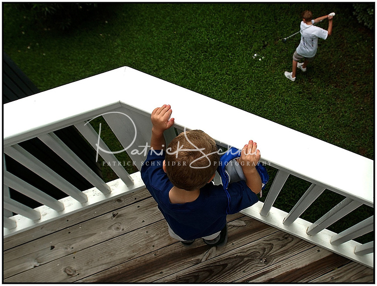 A young boy watches over the railing as an older boy practices his golf swing.  Model released image may be used to illustrate other destinations or concepts.