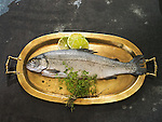 Whole salmon, raw, on gold platter with fresh thyme and lime slices