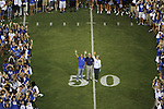Student Government President Stephen Bilas, left, President Eli Capilouto, center, and Mary Lynne Capilouto, right, pose at Big Blue U at Commonwealth Stadium on Saturday, August 18, 2012. Students were invited to come learn the cheers and fight song and then pose for a picture on the field. Photo by Tessa Lighty | Staff
