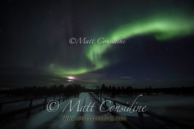 Nothern lights over snow covered road. (Photo by Travel Photographer Matt Considine)