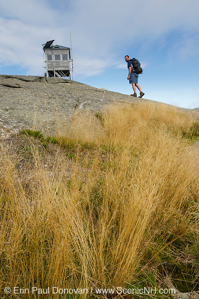 Mount Cardigan State Park - A hiker near Cardigan Mountain Tower on Cardigan Mountain in Orange , New Hampshire USA. This fire tower was in operation from 1924-present
