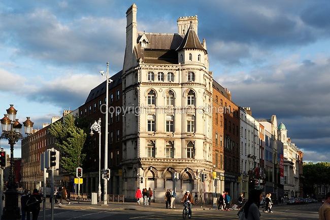 Low angle view looking South from O'Connell Bridge, showing the junction of D'Olier Street (left), and Westmoreland Street (right), Dublin, Ireland. The top floor apartment of this typical Victorian building was once owned (if not still) by U2's Adam Clayton. Picture by Manuel Cohen