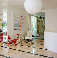 One red and one white Eames chair beneath an Alvis Vega colour-field painting in the entrance to the living area