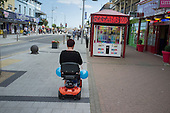 Woman on a mobility scooter in Clacton.  The resort is the second most deprived seaside town in the UK.