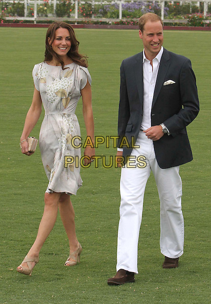 Catherine, Duchess of Cambridge & Prince William, Duke of Cambridge .Audi At The Foundation Polo Challenge held at the Santa Barbara Polo & Racquet Club, Santa Barbara, California, USA, 9th July 2011..royal royalty princess Kate Middleton  tour  America full length grey gary floral print dress grass walking beige nude shoes clutch bag green leaves married couple husband wife navy blue blazer jacket white trousers shirt .CAP/ADM/KB.©Kevan Brooks/AdMedia/Capital Pictures.