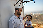 Ezri with his son at home's backyard, in the Israeli settlement of Yitzhar, West Bank.