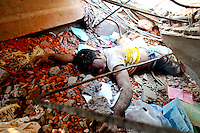 A dead worker lies in the rubble of the collapsed Rana Plaza complex in Savar amid concret rubble and steel girders. The 8 storey building, which housed a number of garment factories employing over 3,000 workers, collapsed on 24 April 2013. By 29 April, at least 380 were known to have died while hundreds remained missing. Workers who were worried about going to work in the building when they noticed cracks in the walls were told not to worry by the building's owner, Mohammed Sohel Rana, who is a member of the ruling Awami League's youth front. He fled his home and tried to escape to neighbouring India after the building collapsed but was caught by police and brought back to Dhaka. Some of the factories working in the Rana Plaza building produce cheap clothes for various European retailers including Primark in the UK and Mango, a Spanish label. . /Felix Features