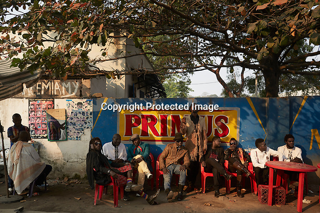"""KINSHASA, DEMOCRATIC REPUBLIC OF CONGO - July 16: Sapeurs from the group Leopard de la Sape relaxes at an outside bar show on July 16, 2014, in Kinshasa, DRC. The word Sapeur comes from SAPE, a French acronym for Société des Ambianceurs et Persons Élégants or Society of Revellers and Elegant People and it also means, to dress with elegance and style"""". Most of the young Sapeurs are unemployed, poor and live in harsh conditions in Kinshasa, a city of about 10 million people. For many of them being a Sapeur means they can escape their daily struggles and dress like fashionable Europeans. Many hustle to build up their expensive collections. Most Sapeurs could never afford to visit Paris, and usually relatives send or bring clothes back to Kinshasa. (Photo by Per-Anders Pettersson)"""