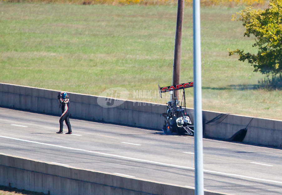 Oct 15, 2017; Ennis, TX, USA; NHRA top fuel driver Steve Torrence walks away after blowing a tire and crashing his dragster in the second round of the Fall Nationals at the Texas Motorplex. Torrence walked away from the crash. Mandatory Credit: Mark J. Rebilas-USA TODAY Sports