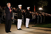 United States President George W. Bush (L) stands for the National Anthem at a military parade with Michael W. Hagee (C), commandant of the Marine Corps, and Col. Terry M. Lockard  May 5, 2006, at the Marine Barracks on Capitol Hill in Washington, DC. A House panel this week approved a measure that would increase funding to add 5,000 more Marines, bringing the overall troop size for the Corps to 180,000. <br /> Credit: Joshua Roberts / Pool via CNP
