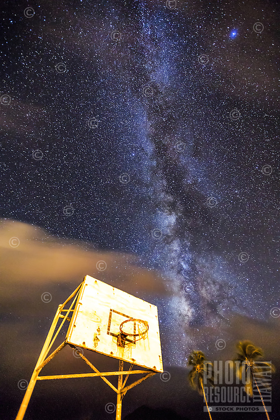 The Milky Way shines above a basketball goal and palm trees at a Hanalei playground, Kaua'i.