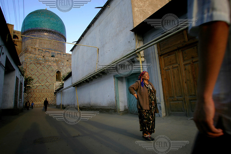 A woman stands in a street behind one of the great madrasahs that enclose the Registan (square).