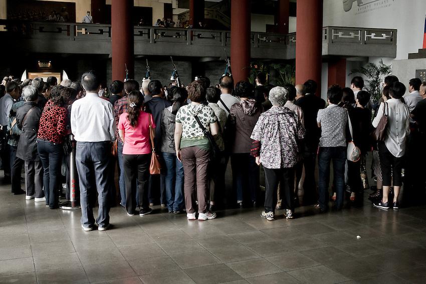 Un groupe de touristes chinois du continent assiste a la relève de la garde face à la statue géante de Sun-Yat Sen dans le musée qui lui est dedié à Taipei.